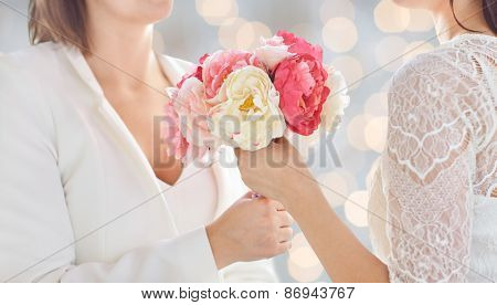 people, homosexuality, same-sex marriage and love concept - close up of happy married lesbian couple with flower bunch over holidays lights background