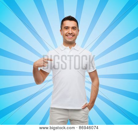 happiness, advertisement, fashion, gesture and people concept - smiling man in t-shirt pointing finger on himself blue burst rays background