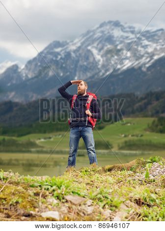 travel, tourism, hike and people concept - tourist with beard, backpack standing on edge of hill and looking far away over mountains background