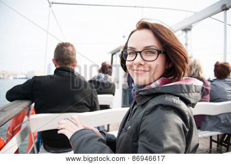 Young woman sitting on boat, looking at camera and smiling