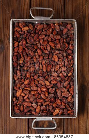 roasted cocoa chocolate beans in Vintage heavy cast aluminum roasting pan on wood background