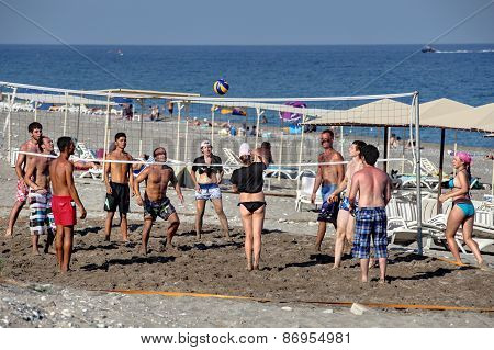 Group Of Tourists Playing Beach Volleyball.