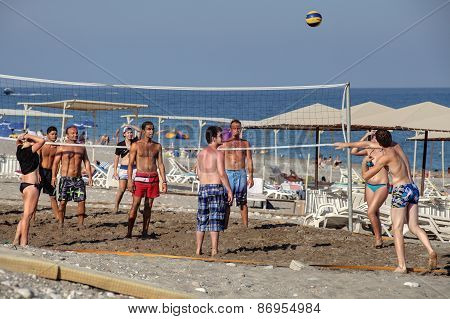 Vacationer Playing Volleyball On The Private Beach Resort.