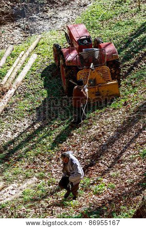 Two Old Man Working With A Tractor In Forest