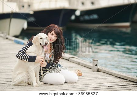Portrait of beautiful young woman sitting with a dog in the Harbor near the yacht club.