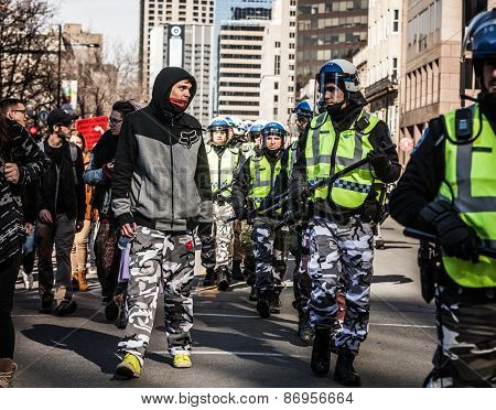 Policeman And Protester Looking Each Other In The Eyes And Wearing The Same Army Pants
