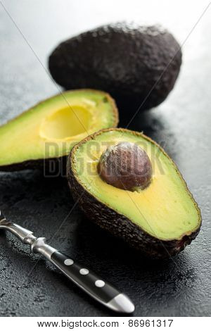 halved avocado on old black table
