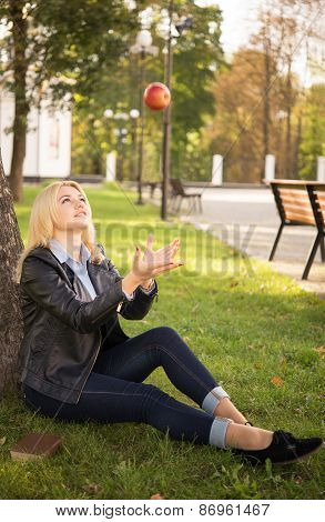 Beautiful Girl Catches An Apple Near The Tree
