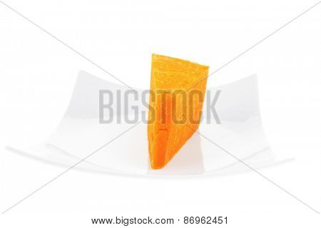 piece of french cheddar cheese on a ceramic plate isolated over white background