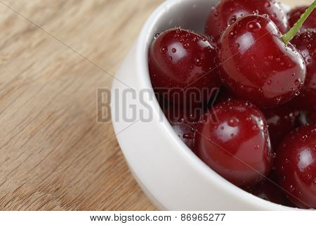 ripe cherry berries in white bowl on wood table