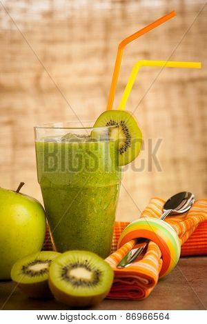 Healthy green Smoothie served in a glass decorated with two color straws