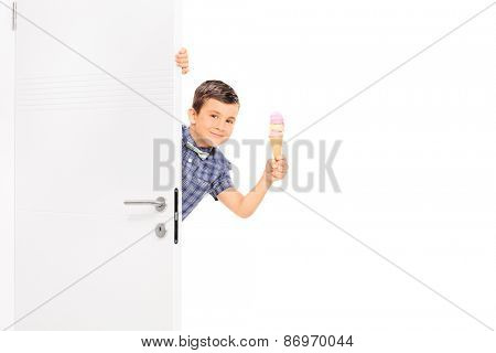 Little boy holding and ice cream behind a white door and looking at the camera isolated on white background