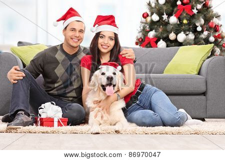 Young couple celebrating Christmas together with their dog seated by the sofa at home