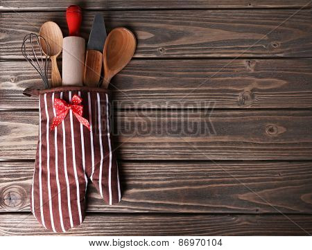 Set of kitchen utensils in mitten on wooden planks background