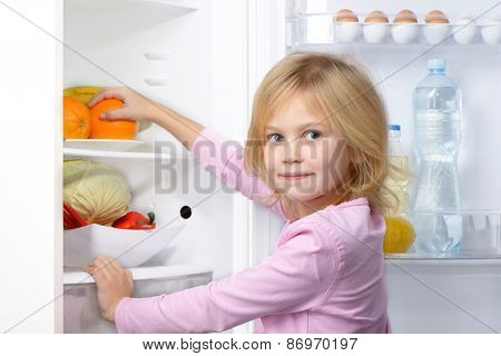 Little girl looking at camera and picking food from fridge