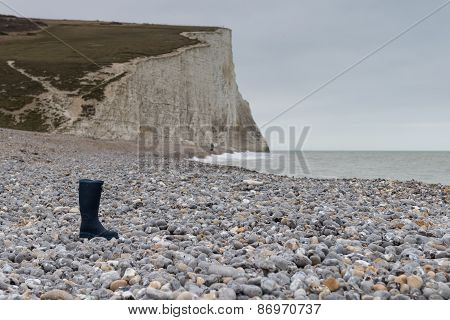 Lone boot on a beach of shingle