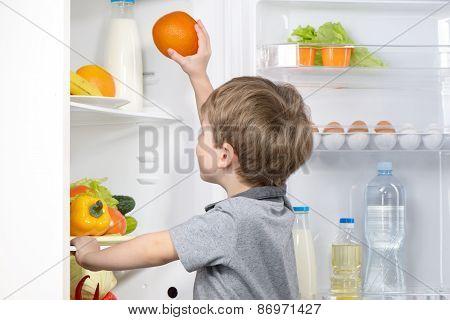 Little cute boy picking orange from fridge
