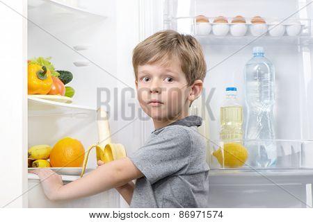 Little cute boy holding banana near open fridge