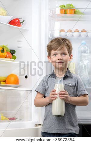 Cute boy holding bottle of milk near open fridge