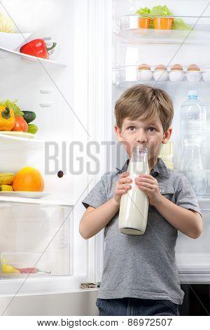 Little cute boy drinking milk near open fridge
