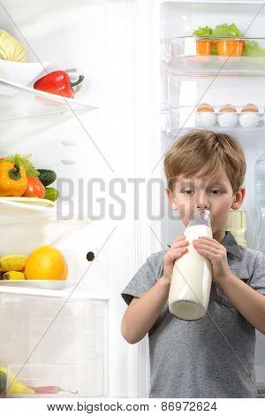 Cute boy drinking milk near open fridge