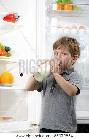 Funny little boy drinking milk near open fridge
