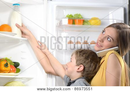 Mother with phone helping son to get milk from fridge