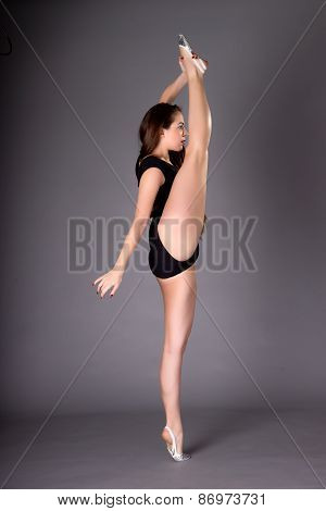 Young Female Contortionist Dances, On Dark Background