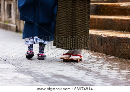 Close up of mother and daughter wearing kimono and geta traditional Japanese footwear.