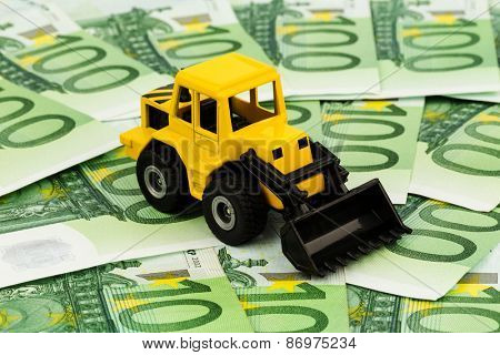 an excavator stands on euro banknotes. symbolic photo for cost, revenue and grants in the construction industry and the construction industry