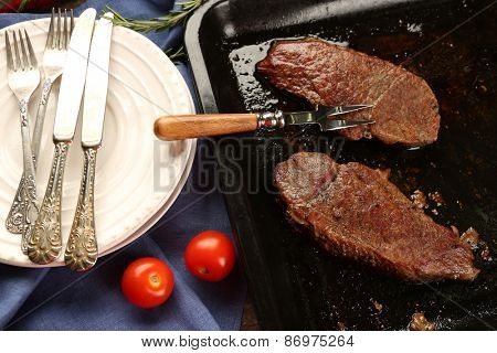 Composition with tasty roasted meat on pan, tomatoes and rosemary sprigs on wooden background