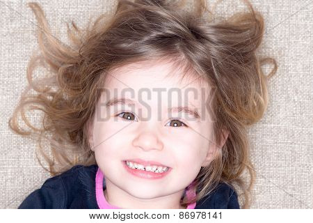 Headshot Of Young Girl Lying On A Carpet
