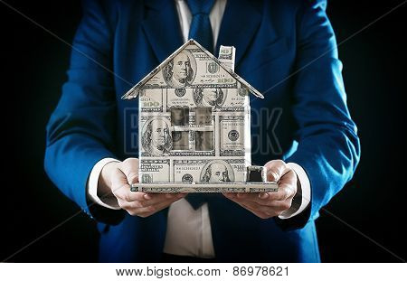 Model of house made of money in male hands on black background