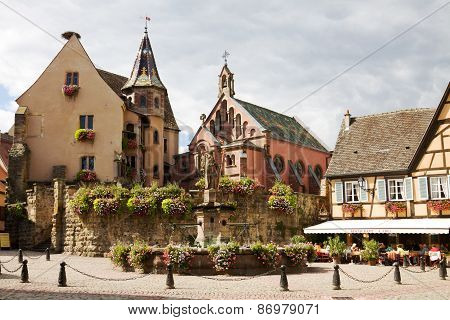 Castle, Church And Fountain Named Saint Leon On The Central Square Of Eguisheim Village In France