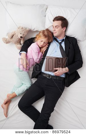 Top view of businessman with book and his sleeping daughter