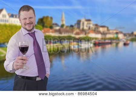 Businessman holding glass of wine with cityscape in background