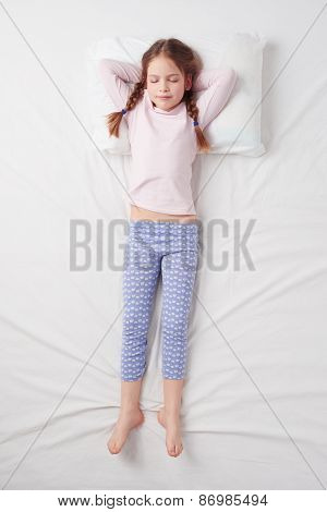 Top view of little cute girl sleeping in Soldier pose