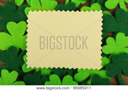 Greeting card for Saint Patrick's Day with shamrocks and wooden table background