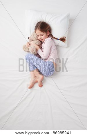 Top view of little cute girl sleeping with teddy bear