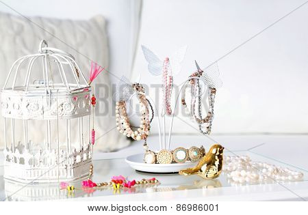 Decorative stand with jewelry and bijouterie on table in room