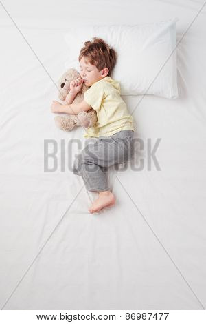 Top view of little boy sleeping in Foetus pose