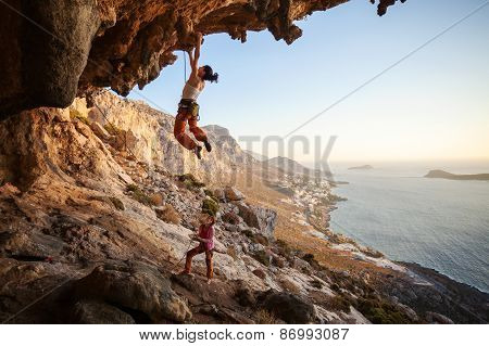 Young woman lead climbing on overhanging cliff