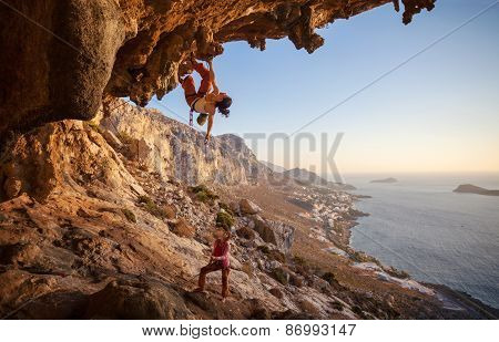 Young woman lead climbing along a roof in cave