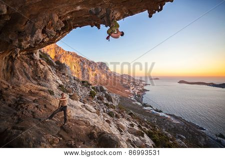 Male rock climber climbing on a roof in a cave