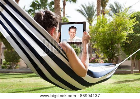 Woman In Hammock With Digital Tablet
