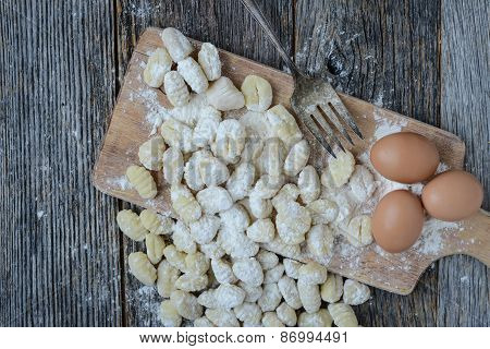 Gnocchi On Cutting Board And Rustic Wood Background