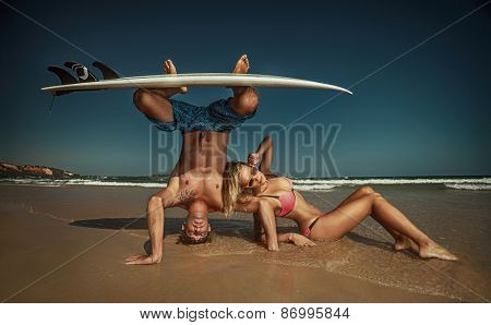 Cheerful surfing couple posing on the beach