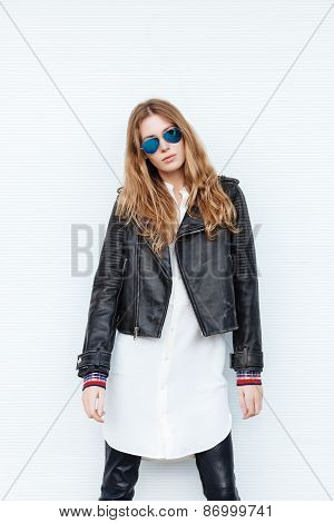 Young beautiful fashionable woman in leather jacket and white blouse posing outdoors against garage