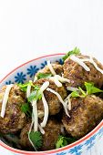 foto of cilantro  - Homemade Italian meatballs garnished with cilantro and parmesan cheese in a small bowl - JPG