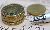 stock photo of british pound sterling note  - Currencies on graph with a pen on paper - JPG